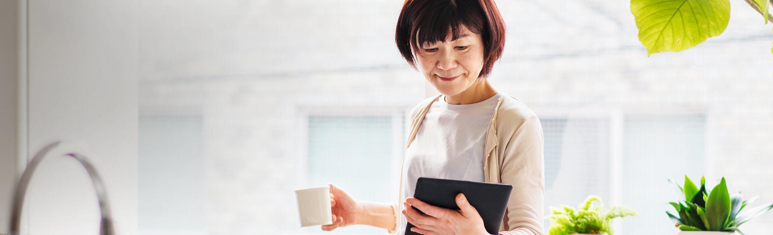 Woman holding coffee mug and tablet